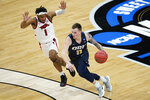 Oral Roberts guard Carlos Jurgens (11) drives up court ahead of Arkansas guard JD Notae (1) during the first half of a Sweet 16 game in the NCAA men's college basketball tournament at Bankers Life Fieldhouse, Saturday, March 27, 2021, in Indianapolis. (AP Photo/Darron Cummings)