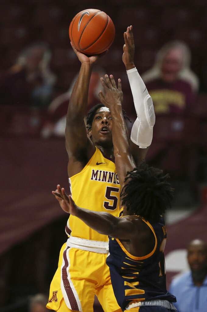 Minnesota guard Marcus Carr (5) shoots over UMKC guard Franck Kamgain during the first half of an NCAA college basketball game Thursday, Dec. 10, 2020, in Minneapolis. (AP Photo/Stacy Bengs)