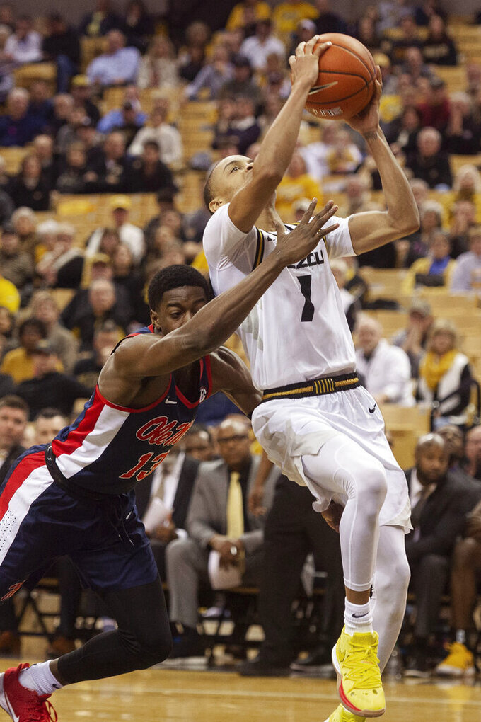Missouri's Xavier Pinson, right, is fouled by Mississippi's Bryce Williams, left, as he shoots during the second half of an NCAA college basketball game Tuesday, Feb. 18, 2020, in Columbia, Mo. Missouri won 71-68.(AP Photo/L.G. Patterson)