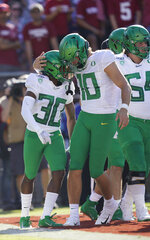Oregon wide receiver Jaylon Redd (30) is congratulated by quarterback Justin Herbert (10) after scoring a touchdown against Stanford during the first half of an NCAA college football game on Saturday, Sept. 21, 2019, in Stanford, Calif. (AP Photo/Tony Avelar)