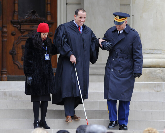 FILE - In this Jan. 1, 2015, file photo, new Michigan Supreme Court Justice Richard Bernstein is helped down the steps during inauguration ceremonies for incoming officials at the state Capitol in Lansing, Mich. Bernstein said Thursday, April 8, 2021, that he has been overseas for three months, participating in an international program to improve the perception of people with disabilities while pulling all-nighters to keep up with his work back home. (David Coates/Detroit News via AP, File)