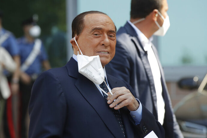 FILE - In this Sept. 14, 2020 file photo, Italian former Premier Silvio Berlusconi adjusts his face mask as he leaves the San Raffaele hospital after testing positive for COVID-19, in Milan, Italy. Berlusconi, 84, was released Friday, Jan. 15, 2021 from a hospital in the principality of Monaco, where he underwent medical tests for heart problems, his press office said. (AP Photo/Luca Bruno, file)