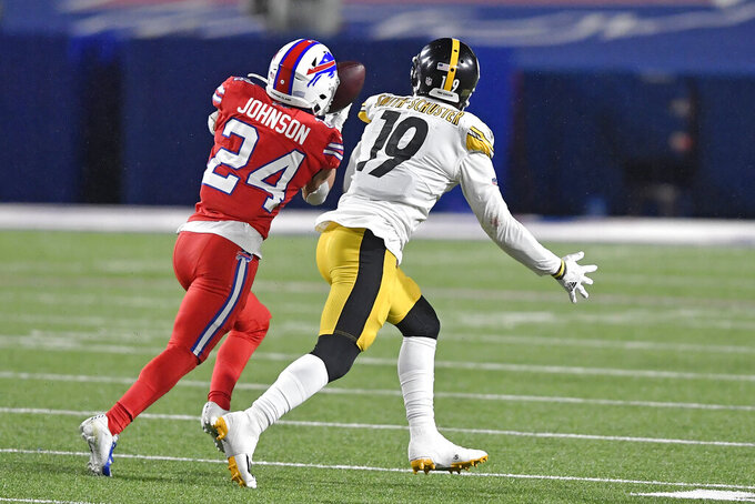 Buffalo Bills cornerback Taron Johnson (24) intercepts a pass intended for Pittsburgh Steelers wide receiver JuJu Smith-Schuster (19) and returns it for a 51-yard touchdown during the first half of an NFL football game in Orchard Park, N.Y., Sunday, Dec. 13, 2020. (AP Photo/Adrian Kraus)
