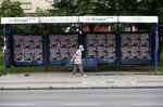In this photo taken on Tuesday, June 16, 2020, a man wearing a face mask to protect against coronavirus passes by election posters showing Serbian Right leader Misa Vacic, reading: ''We know each other well, we grew up together!'', in Belgrade, Serbia. Most of the main opposition parties will boycott the election because of what they say is Serbian President Aleksandar Vucic's iron grip on the country's media and the electoral process, as well as potential coronavirus infection hazards at voting stations. Vucic and his allies have denounced the boycott. (AP Photo/Darko Vojinovic)