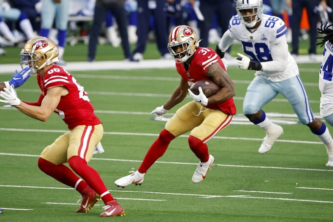 San Francisco 49ers running back Raheem Mostert (31) carries the ball as Dallas Cowboys defensive end Aldon Smith (58) gives chase in the first half of an NFL football game in Arlington, Texas, Sunday, Dec. 20, 2020. (AP Photo/Michael Ainsworth)