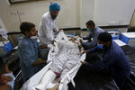 People shifts a woman, who was injured in bus and train accident, into bed after receiving initial treatment at a hospital in Sheikhupura near Lahore, Pakistan, Friday, July 3, 2020. A passenger train crashed into a bus carrying Sikh pilgrims at an unmanned railway crossing in eastern Pakistan, police and rescue officials said. (AP Photo/K.M. Chaudary)