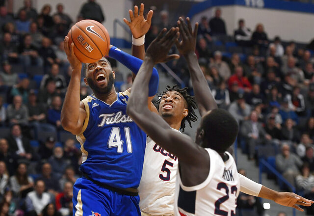 Tulsa's Jeriah Horne (41) is fouled by Connecticut's Isaiah Whaley (5) as Connecticut's Akok Akok (23) defends in the first half of an NCAA college basketball game, Sunday, Jan. 26, 2020, in Hartford, Conn. (AP Photo/Jessica Hill)