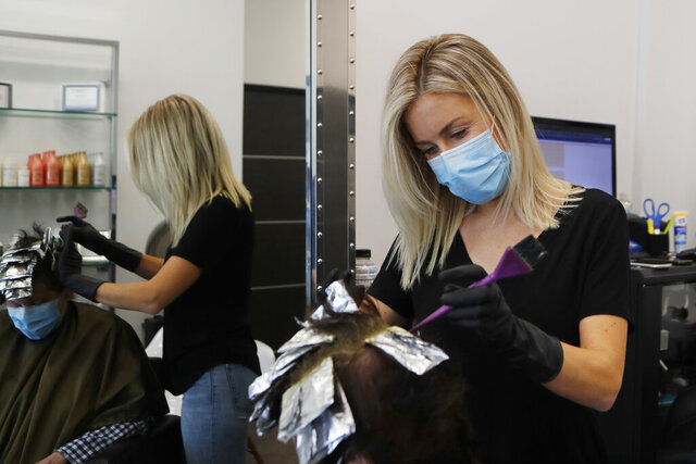 Stylist Mandi Streeter works on a customer, Monday, June 15, 2020, in Royal Oak, Mich. Monday was the first day barbershops and salons were allowed to operate after being closed since March 22 to curb the coronavirus. (AP Photo/Carlos Osorio)