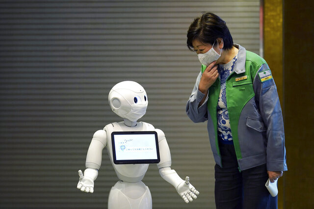 A humanoid robot Pepper wearing a face mask greets Tokyo Gov. Yuriko Koike at the lobby of a hotel for the new coronavirus COVID-19 patients with mild symptoms during a media preview in Tokyo Friday, May 1, 2020. Prime Minister Shinzo Abe said Thursday he planned to extend a state of emergency beyond the scheduled end of May 6 because infections are spreading and hospitals are overburdened. (AP Photo/Eugene Hoshiko)