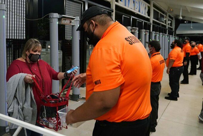 A security officer checks a fan arriving for an NCAA College Football Playoff national championship game between Alabama and Ohio State Monday, Jan. 11, 2021, in Miami Gardens, Fla. (AP Photo/Lynne Sladky)