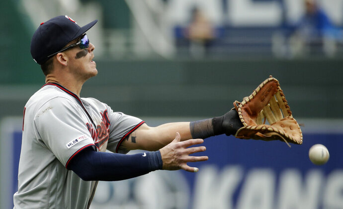 Minnesota Twins first baseman Tyler Austin can't make the catch on a single by Kansas City Royals' Martin Maldonado during the eighth inning of a baseball game Wednesday, April 3, 2019, in Kansas City, Mo. (AP Photo/Charlie Riedel)