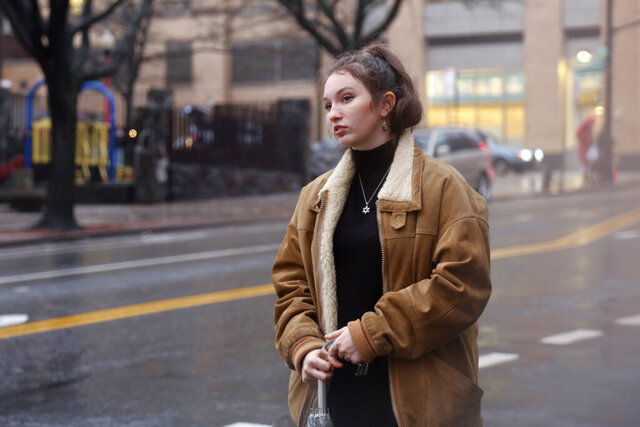 In this Dec. 30, 2019, photo, Shoshana Blum, a 20-year-old junior at City College of New York, waits for a taxi in New York. Despite having been victim to a verbal and physical anti-Semitic attack on the subway, Blum wears her Star of David pendant, a visible marker of her Jewish identity, proudly. (AP Photo/Emily Leshner)