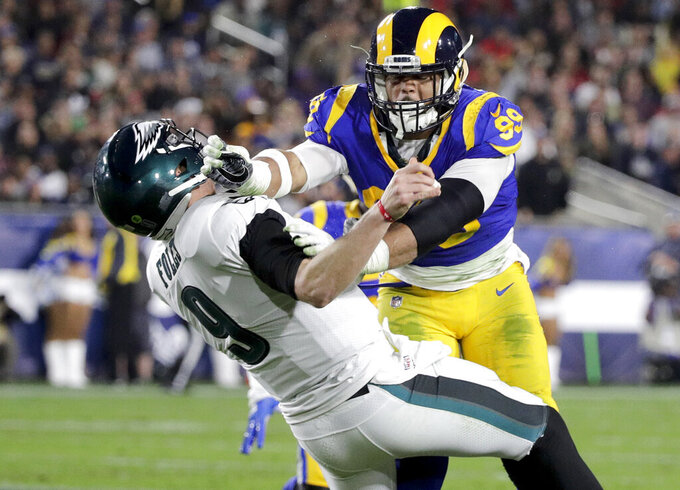 FILE - In this Dec. 16, 2018, file photo, Los Angeles Rams defensive end Aaron Donald hits Philadelphia Eagles quarterback Nick Foles after Foles threw the ball away during the first half in an NFL football game in Los Angeles. The Rams know they've got to pressure Tom Brady early and often to have a chance in the Super Bowl, and they've been assembling the tools for this job all year long. They signed Ndamukong Suh to a big free-agent deal, wrote a record-breaking contract for Aaron Donald and acquired edge rusher Dante Fowler from Jacksonville down the stretch. (AP Photo/Jae C. Hong, File)