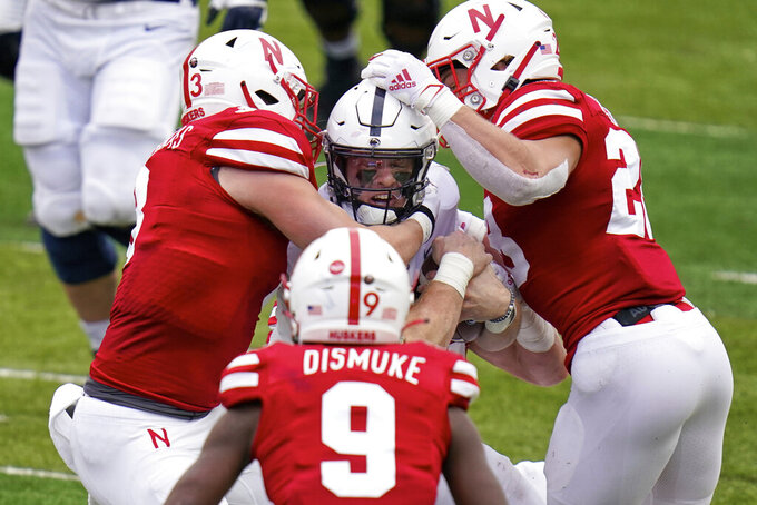 Nebraska linebackers Will Honas (3), Luke Reimer (28), and safety Marquel Dismuke (9) tackle Penn State quarterback Will Levis (7) during the second half of an NCAA college football game in Lincoln, Neb., Saturday, Nov. 14, 2020. Nebraska won 30-23. (AP Photo/Nati Harnik)