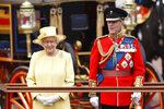 FILE - In this file photo dated Saturday, June 16, 2012, Britain's Queen Elizabeth II, and Prince Philip take a salute as the Guards march past outside Buckingham Palace after the Trooping The Color parade at Horse Guards Parade in London. Trooping the Colour is an annual ceremony marking the queen's official birthday, which takes place in June. The monarch's actual birthday was on 21 April, when she turned 86. Prince Philip who died Friday April 9, 2021, aged 99, lived through a tumultuous century of war and upheavals, but he helped forge a period of stability for the British monarchy under his wife, Queen Elizabeth II. (AP Photo/Sang Tan, FILE)