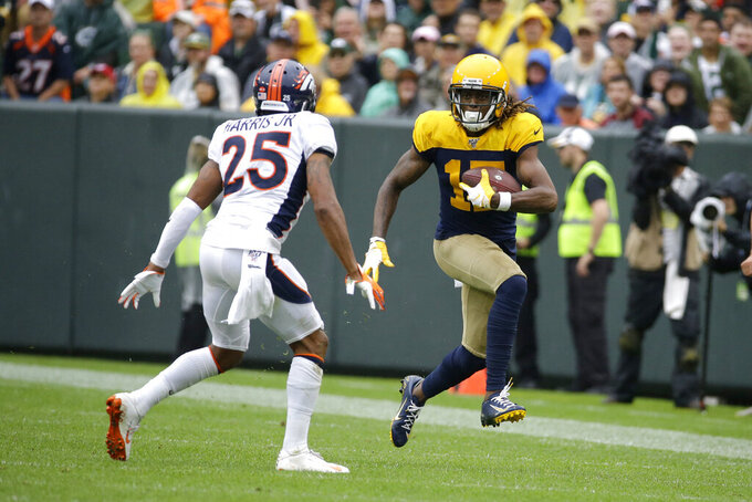 Green Bay Packers wide receiver Davante Adams, right, runs with the ball after catching a pass as Denver Broncos cornerback Chris Harris (25) defends during the second half of an NFL football game Sunday, Sept. 22, 2019, in Green Bay, Wis. (AP Photo/Mike Roemer)