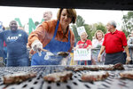 Democratic presidential candidate Sen. Amy Klobuchar works the grill during the Polk County Democrats Steak Fry, Saturday, Sept. 21, 2019, in Des Moines, Iowa. (AP Photo/Charlie Neibergall)