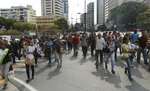 People walk home during a power outage that suspended the subway in Caracas, Venezuela, Monday, March 25, 2019. (AP Photo/Fernando Llano)