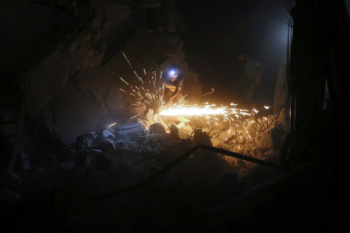 This photo released Wednesday, Aug. 28, 2019 by the opposition Syrian Civil Defense rescue group, also known as White Helmets, which has been authenticated based on its contents and other AP reporting, shows a civil defense worker cuting metal to reach survivors after airstrikes hit the northern town of Maaret al-Numan, in Idlib province, Syria. Idlib is the Syrian opposition's final stronghold. The opposition Syrian Civil Defense group of first responders said airstrikes on Maaret al-Numan on Wednesday killed 12 people and wounded 34. (Syrian Civil Defense White Helmets via AP)