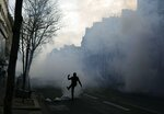 A demonstrator kicks away a teargas canister during small clashes with police in Paris, Saturday, March 23, 2019. The French government vowed to strengthen security as yellow vest protesters stage a 19th round of demonstrations, in an effort to avoid a repeat of last week's riots in Paris. (AP Photo/Kamil Zihnioglu)