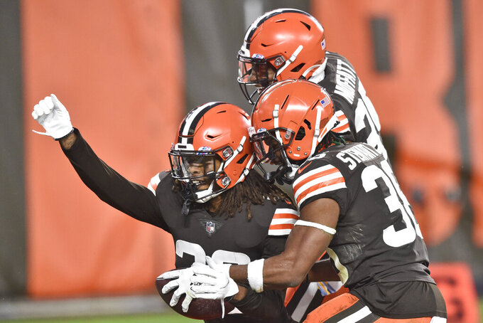 Cleveland Browns safety Sheldrick Redwine, left, celebrates with teammates after an interception during the second half of an NFL football game against the Indianapolis Colts, Sunday, Oct. 11, 2020, in Cleveland. The Browns won 32-23. (AP Photo/David Richard)