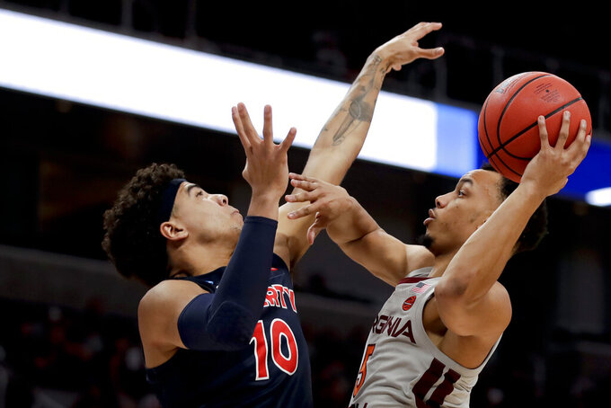 Virginia Tech guard Justin Robinson, right, shoots over Liberty guard Elijah Cuffee during the first half of a second-round game in the NCAA men's college basketball tournament Sunday, March 24, 2019, in San Jose, Calif. (AP Photo/Ben Margot)