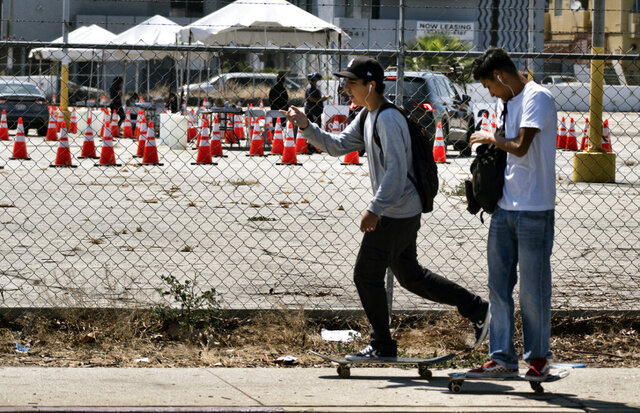 Skateboarders ride past a coronavirus testing site in the Panorama City section of Los Angeles on Tuesday, Aug. 3, 2020. A technical problem has caused a lag in California's tally of coronavirus test results, casting doubt on the accuracy of recent data showing improvements in the infection rate and hindering efforts to track the spread. (AP Photo/Richard Vogel)