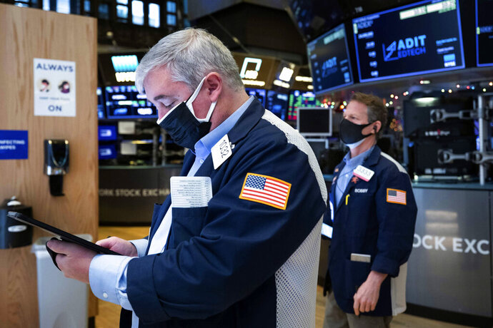 In this photo provided by the New York Stock Exchange, traders Edward MacCarthy, left, and Robert Charmak work on the trading floor, Tuesday, Jan. 12, 2021. U.S. stocks are drifting near their record heights Tuesday, while Treasury yields keep marching higher amid expectations that the economy will pull out of its slump after a powerful recovery sweeps the globe later this year. (Colin Ziemer/New York Stock Exchange via AP)