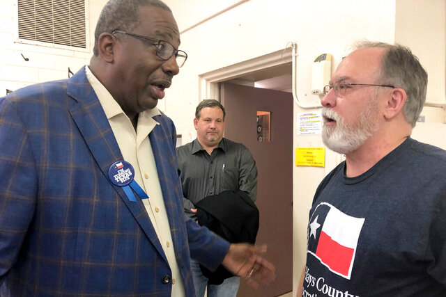 In this Sunday, Dec. 8, 2019 photo, Democrat Royce West, left, a Texas state senator who is running for U.S. Senate in Texas, talks with local party organizer Jimmy Alan Hall after a campaign stop in San Marcos, Texas. West is one of a dozen Democrats in Texas running to challenge Republican incumbent John Cornyn in 2020. (AP Photo/Paul Weber)