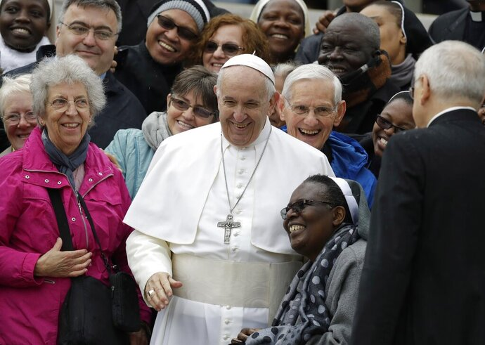 Pope Francis shares a laugh with a group of faithful as he poses for a family photo, at the end of his weekly general audience in St. Peter's Square, at the Vatican, Wednesday May 15, 2019. (AP Photo/Andrew Medichini)