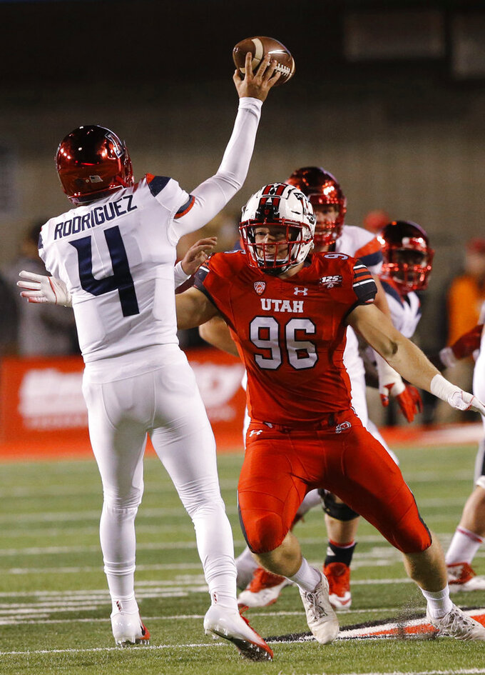 Utah defensive end Nick Heninger (96) hurries the pass from Arizona quarterback Rhett Rodriguez (4) during the first half of an NCAA college football game Friday, Oct. 12, 2018, in Salt Lake City. (AP Photo/Rick Bowmer)