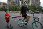 A man pulls a child along as they wear masks to curb the spread of the new coronavirus on the streets of Beijing,  Saturday, May 30, 2020. (AP Photo/Ng Han Guan)