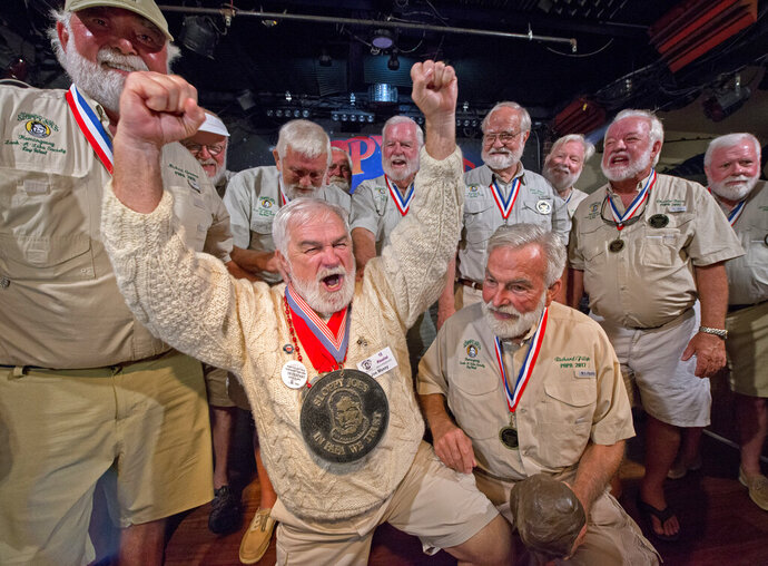 In this Saturday, July 20, 2019, photo provided by the Florida Keys News Bureau, Joe Maxey, second from left, celebrates his victory at the Hemingway Look-Alike Contest at Sloppy Joe's Bar in Key West, Fla. Competing for the eighth time, Maxey beat 141 other contestants to claim top honors. The competition highlighted activities during the yearly Hemingway Days festival that honors author Ernest Hemingway, who lived in Key West during the 1930s. (Andy Newman/Florida Keys News Bureau via AP)