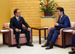 Okinawa Governor Denny Tamaki, left, meets with Japanese Prime Minister Shinzo Abe at Abe's office in Tokyo Friday, Oct. 12, 2018. Tamaki won the election for governor at the end of last month, becoming the first Amerasian to lead the southwestern Japanese islands. (AP Photo/Eugene Hoshiko, Pool)