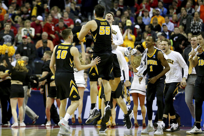 Iowa forward Luka Garza (55) and teammates celebrates after a first-round game against Cincinnati in the NCAA men's college basketball tournament, Friday, March 22, 2019, in Columbus, Ohio. Iowa won 79-72. (Kareem Elgazzar/The Cincinnati Enquirer via AP)