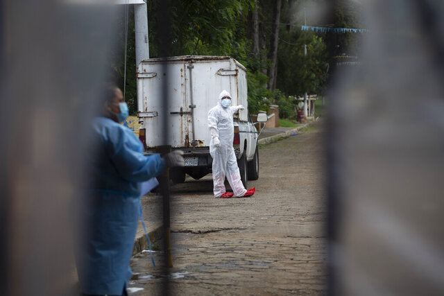 Funeral home worker Manuel Castro, wearing a full protective gear to protect himself from the spread of the new coronavirus, waits to enter La Verbena cemetery in Guatemala City, Wednesday, July 29, 2020. (AP Photo/Moises Castillo)
