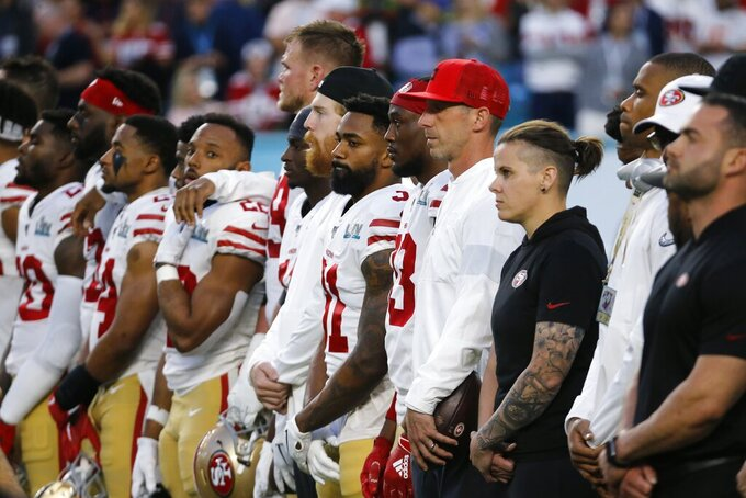 San Francisco 49ers head coach Kyle Shanahan, center, stands next to offensive assistant Katie Sowers and players before the NFL Super Bowl 54 football game between the San Francisco 49ers and Kansas City Chiefs Sunday, Feb. 2, 2020, in Miami Gardens, Fla. (AP Photo/Mark Humphrey)