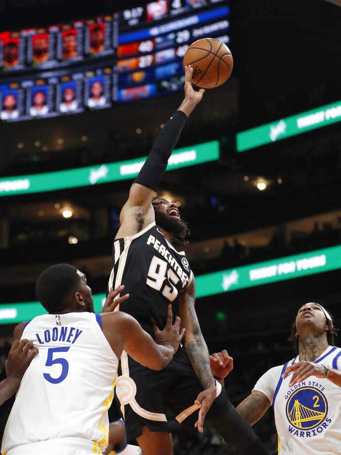 Atlanta Hawks guard DeAndre' Bembry (95) shoots as Golden State Warriors forward Kevon Looney (5) defends in the first half of an NBA basketball game Monday, Dec. 2, 2019, in Atlanta. (AP Photo/John Bazemore)
