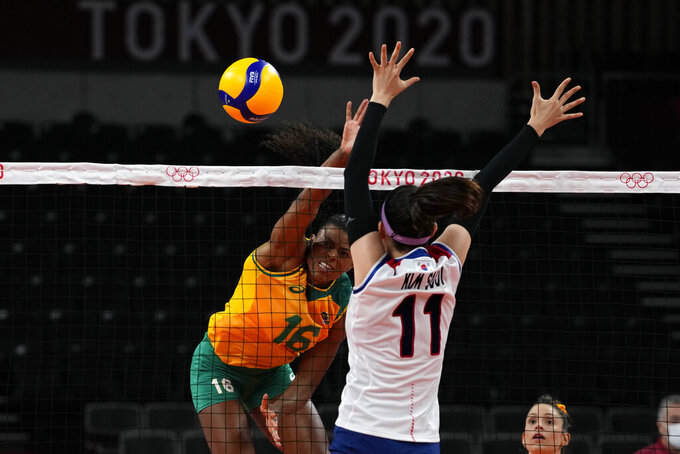 Brazil's Fernanda Rodrigues, left, hits the ball past Korea's Kim Su Ji during the women's volleyball semifinal match between Brazil and South Korea at the 2020 Summer Olympics, Friday, Aug. 6, 2021, in Tokyo, Japan. (AP Photo/Frank Augstein)