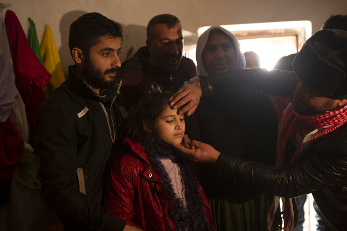 In this Feb. 12, 2020 photo, Malak Saad Dakhel, 11, is anointed by a holy man inside a Yazidi shrine as she is welcomed home by her relatives after her escape from Syria, in Sharia, Iraq. She was captured by Islamic State militants in 2014 and was recently found at al-Hol camp living with a Syrian family. (AP Photo/Maya Alleruzzo)