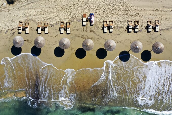 A woman enjoys the sun at Plaka beach on the Aegean island of Naxos, Greece, Friday, May 14, 2021. Greece launched its tourism season Friday amid a competitive scramble across the Mediterranean to lure vacationers emerging from lockdowns. (AP Photo/Thanassis Stavrakis)