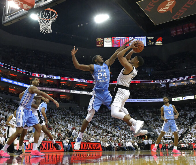 North Carolina guard Kenny Williams (24) attempts to block the shot of Louisville guard Christen Cunningham (1) during the second half of an NCAA college basketball game in Louisville, Ky., Saturday, Feb. 2, 2019. (AP Photo/Timothy D. Easley)