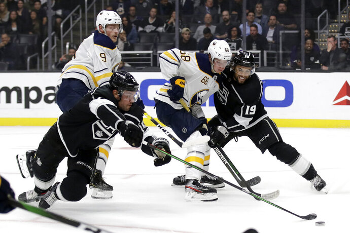 Buffalo Sabres' Victor Olofsson (68) is defended by Los Angeles Kings' Alex Iafallo (19) and Alec Martinez, left, during the first period of an NHL hockey game Thursday, Oct. 17, 2019, in Los Angeles. (AP Photo/Marcio Jose Sanchez)