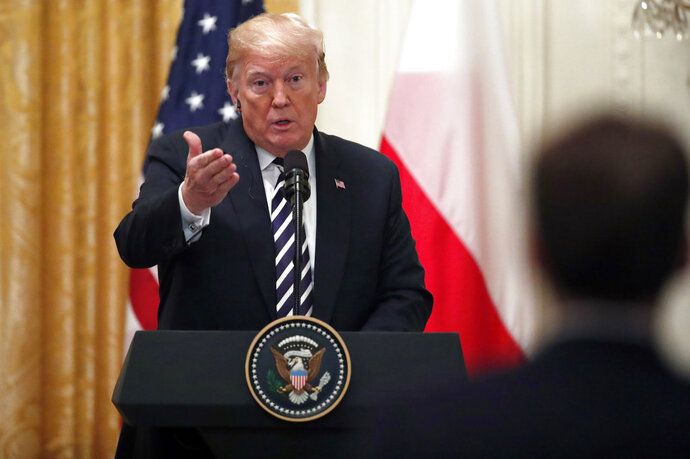 President Donald Trump gestures as he answers a reporter's question during a news conference with Polish President Andrzej Duda, in the East Room of the White House, Tuesday, Sept. 18, 2018, in Washington. (AP Photo/Alex Brandon)