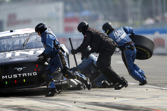 A pit crew works on Josh Bilicki's car during a NASCAR Cup Series auto race in Watkins Glen, N.Y., on Sunday, Aug. 8, 2021. (AP Photo/Joshua Bessex)