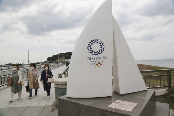 People wearing face masks to protect against the spread of the new coronavirus walk at Enoshima, the venue of sailing competitions at the Tokyo 2020 Olympics, in Fujisawa, near Tokyo, Tuesday, April 6, 2021. Many preparations are still up in the air as organizers try to figure out how to hold the postponed games in the middle of a pandemic. (AP Photo/Koji Sasahara)