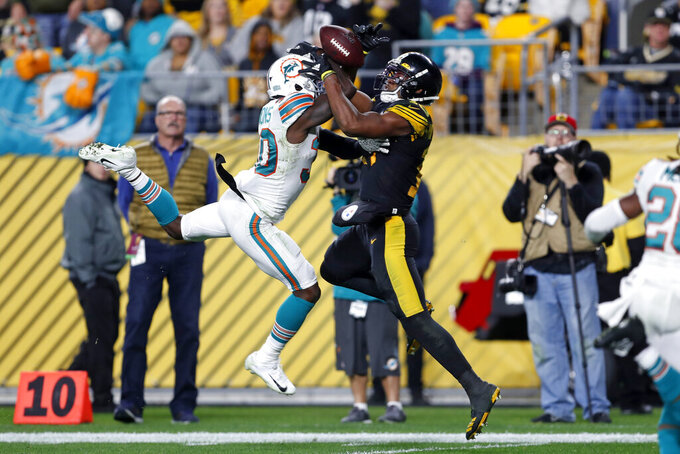 Pittsburgh Steelers wide receiver JuJu Smith-Schuster, center right, hauls in a pass from quarterback Mason Rudolph before taking it for a touchdown with Miami Dolphins defensive back Chris Lammons (30) defending during the second half of an NFL football game in Pittsburgh, Monday, Oct. 28, 2019. (AP Photo/Keith Srakocic)