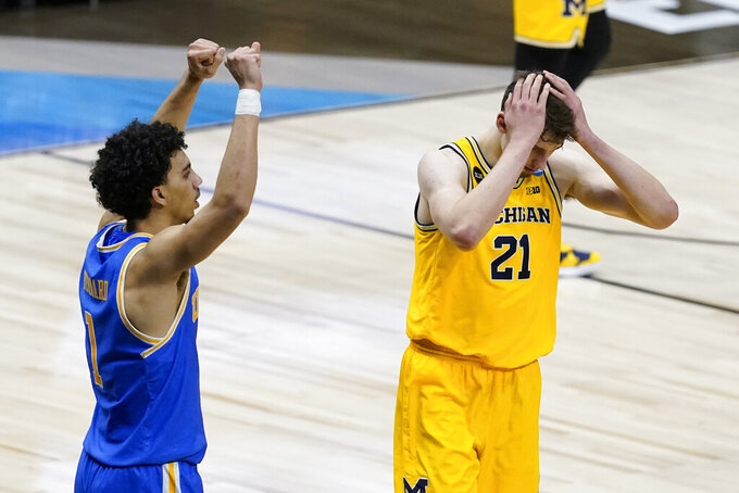 Michigan guard Franz Wagner (21) reacts in front of UCLA guard Jules Bernard, left, after missing a shot at the end of an Elite 8 game in the NCAA men's college basketball tournament at Lucas Oil Stadium, Wednesday, March 31, 2021, in Indianapolis. UCLA won 51-49. (AP Photo/Darron Cummings)