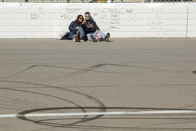 Fans hang out on the track before a NASCAR Cup Series auto race at Kansas Speedway in, Kansas City, Kan. Sunday, Oct. 20, 2019. (AP Photo/Charlie Riedel)