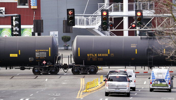 FILE - In this Feb. 13, 2018, file photo, automobile traffic waits at a train crossing as train cars that carry oil are pulled through downtown Seattle. Attorneys general for North Dakota and Montana have petitioned the Trump administration Wednesday, July 17, 2019, to overrule a Washington state law that imposes safety restrictions on oil shipped by rail from the Northern Plains. (AP Photo/Elaine Thompson, File)
